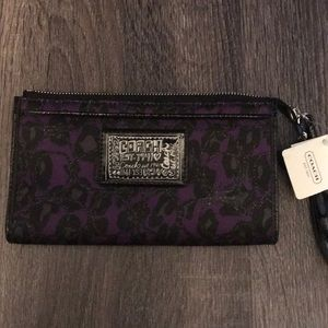 New with tags Coach clutch wallet with wrist band.